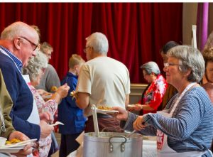 Serving meals at the English food stall in Devizes Corn Exchange
