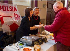 Polish food stallholders serving a man in Devizes Corn Exchange