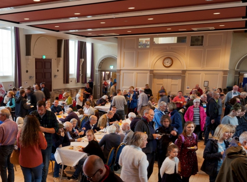 Crowds in Devizes Corn Exchange with tables of people eating world food