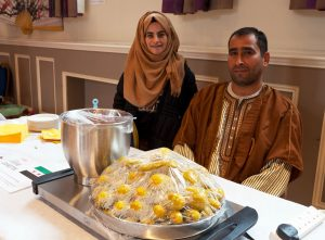Syrian food stallholders at a table with food, Devizes Corn Exchange