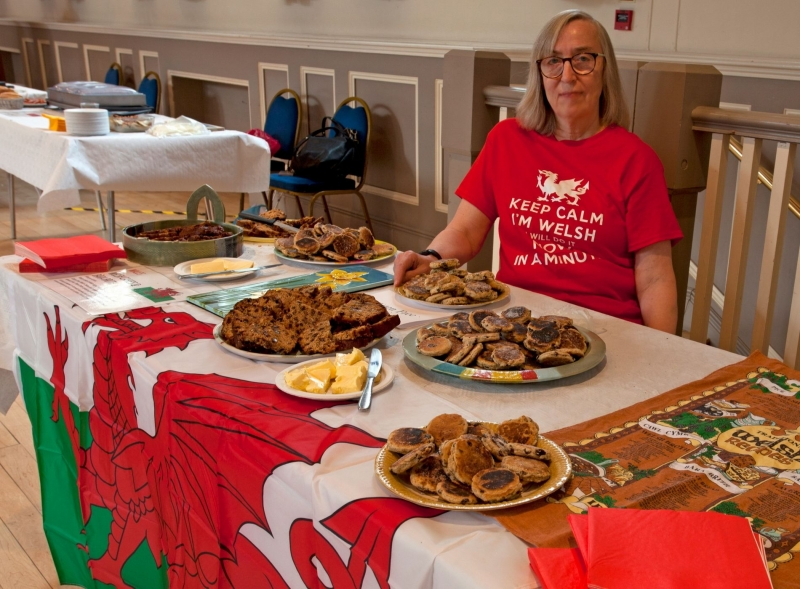 Welsh food stallholder at table with cakes in Devizes Corn Exchange